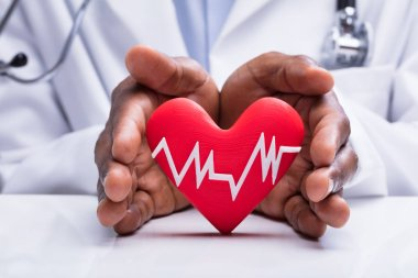Close-up Of Doctor Protecting Heart With White Heartbeat Pulse Icon On White Desk