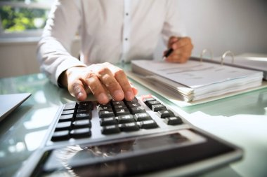 Close-up of a businessman's hand calculating bill in office