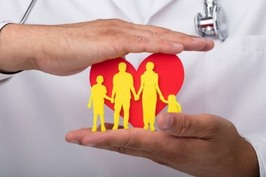 Doctor's hand protecting red heart with yellow family figures