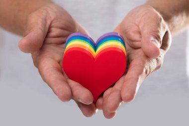Close-up of a man's hand holding LGBT hearts