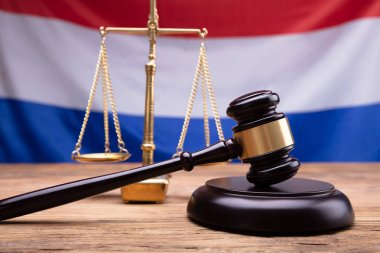 Close-up Of Mallet And Justice Scale On Wooden Desk In Front Of Netherlands Flag