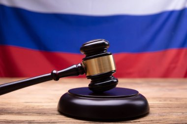 Close-up Of Judge Gavel In Front Of Russian Flag