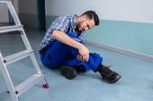 Údržbář dotýká zraněná noha po pádu ze žebříku