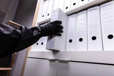 Close-up Of A Thief Stealing Folder From Wooden Shelf