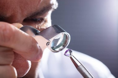 Close-up Of A Male Jeweler's Hand Looking At Diamond Through Magnifying Loupe