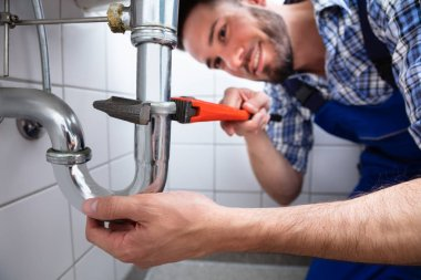 Young Male Plumber Repairing Sink With Adjustable Wrench In Bathroom