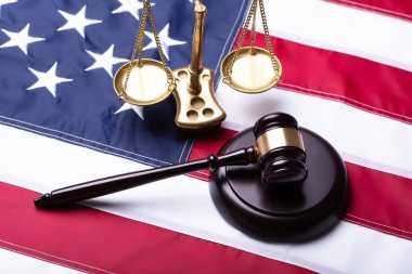 Elevated View Of Gavel And Golden Justice Scale On American Flag