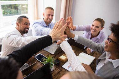 Group Of Happy Young Businesspeople Giving High Five In Office