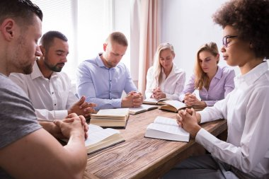 Group Of Young Multiethnic People Reading Bible Over Wooden Desk