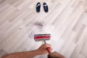 Fotografie Close-up Of Male Janitors Hand Cleaning Dirt On Floor With Broom