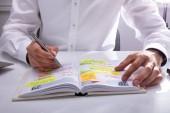 Podnikatel je ruční psaní harmonogram v deníku na kancelářský stůl