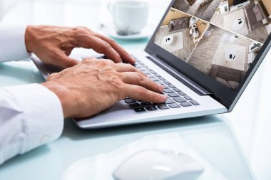 Close-up Of A Businessman's Hand Monitoring CCTV Camera Footage On Laptop