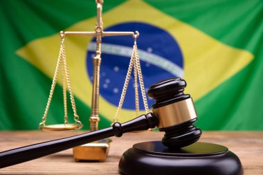 Wooden Mallet And Golden Justice Scale On Wooden Desk In Front Of Brazil Flag