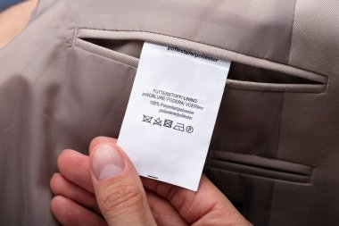 Close-up Of A Man's Hand Holding Trouser Label Showing Caution Tag