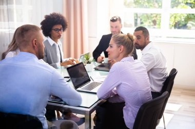 Group Of Businesspeople Sitting In Office During Business Meeting