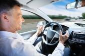 Fotografia Primo piano di un uomo maturo che viaggiano In auto guida auto