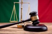 Fotografia Bandiera italiana dietro scala della giustizia e Mallet sullo scrittorio di legno