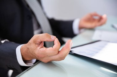 Close-up Of A Businessman's Hand While Meditating In Office