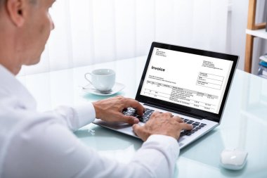 Close-up Of A Businessman Looking At Laptop Over Desk In Office