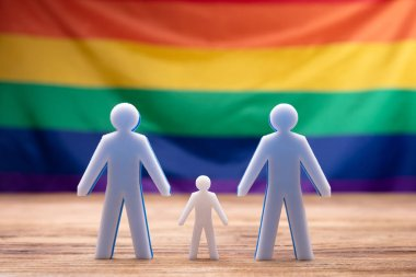 Family Figure Standing On Wooden Desk In Front Of Rainbow Flag