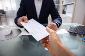 Podnikatel je ruka by šek nad stůl sklo