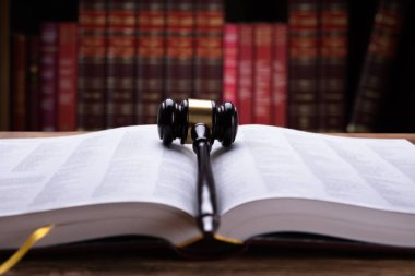 Close-up Of An Open Law Book And Wooden Mallet In Courtroom