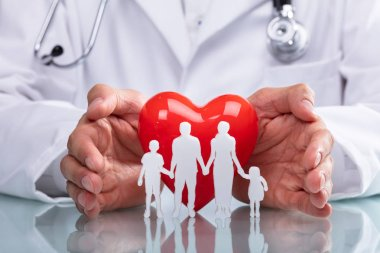 Doctor's Hand Protecting Red Heart With Family Figure On Reflective Desk