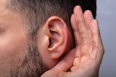 Close-up Of A Man Trying To Hear With Hand Over Ear