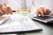 Podnikatel je ručně pomocí kalkulačky během analýzy finanční zpráva s lupou