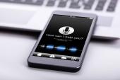 Chytrý telefon na stole s obrazovkou zobrazující, jak vám mohu pomoci? Text