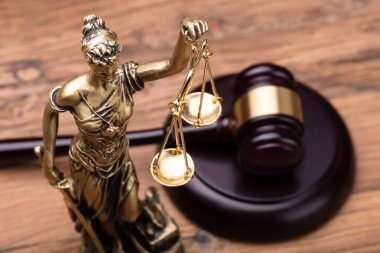Statue Of Justice With Brown Gavel On Wooden Table