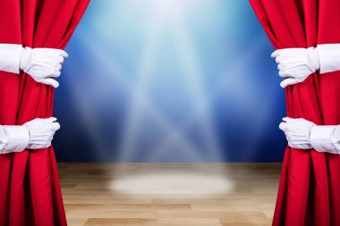 Two People Opening Red Stage Curtain With Three Spot Lights In Background