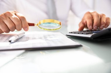 Businessman's Hand Using Calculator While Analyzing Financial Report With Magnifying Glass