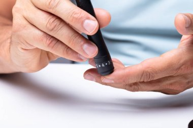 Close-up Of A Man's Hand Testing High Blood Sugar With Glucometer