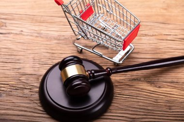 Elevated View Of Judge Gavel And Shopping Cart On Wooden Table