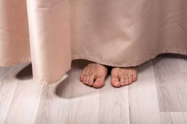 Close-up Of Person's Feet Behind The Curtain