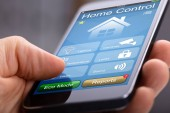 Persons Hand Holding Smart Phone With Home Control Application