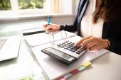 Fotografie Businesswomans Hand Calculating Invoice With Calculator In Office