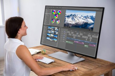 Female Editor Editing Video On Computer Over Wooden Desk
