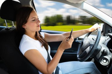 Close-up Of A Woman's Hand Typing Text Message On Cellphone While Driving Car
