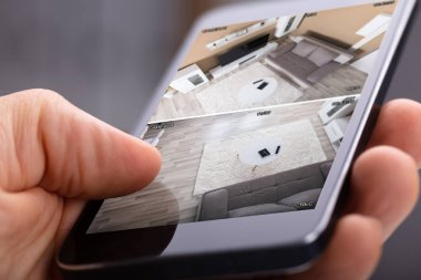 Close Up Of A Person's Hand Using Home Security System On Mobile Phone