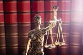 Zlatá barva socha spravedlnosti před červeným právní knihy