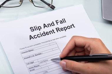 Close-up Of A Woman's Hand Filling Slip And Fall Accident Report