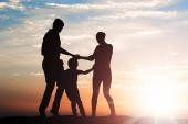 Sziluettjét családi körben tartja kezében a naplemente