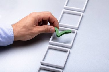 Man's Hand Placing Green Check Mark In Box On Grey Background