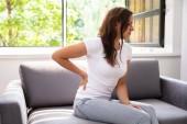 Žena sedí na pohovce trpící bolesti zad