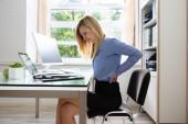 Boční pohled na mladá podnikatelka trpící bolesti zad v úřadu
