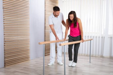 Therapists Assisting Female Patient In Walking With The Support Of Handrails