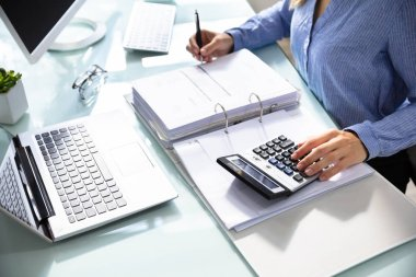 Businesswoman's Hand Calculating Bill With Calculator Over Desk In Office