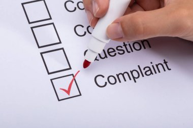 Woman's Hand Ticking Complaint Box On Form With Marker
